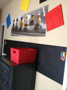 A red basket for hiding diapers sits on top of the dresser with its newly painted red drawer pulls.
