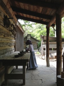 Grinding corn, wheat and coffee by hand outside the Seela Cabin, Log Cabin Village