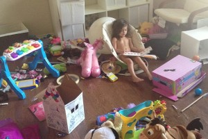 Among the toy chaos, this sweet girl is taking some quiet time to read and collect her thoughts.  Photo courtesy of a fellow DMB contributor.
