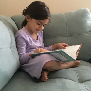 Practicing her newly acquired reading skills.