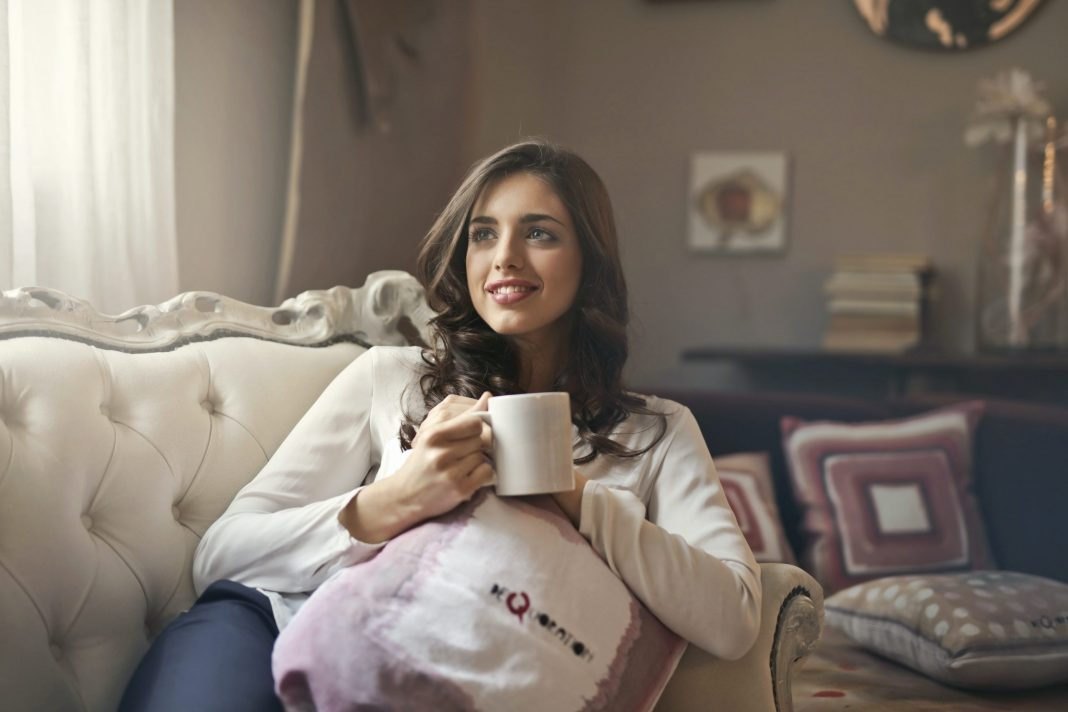 Woman drinking coffee on her couch
