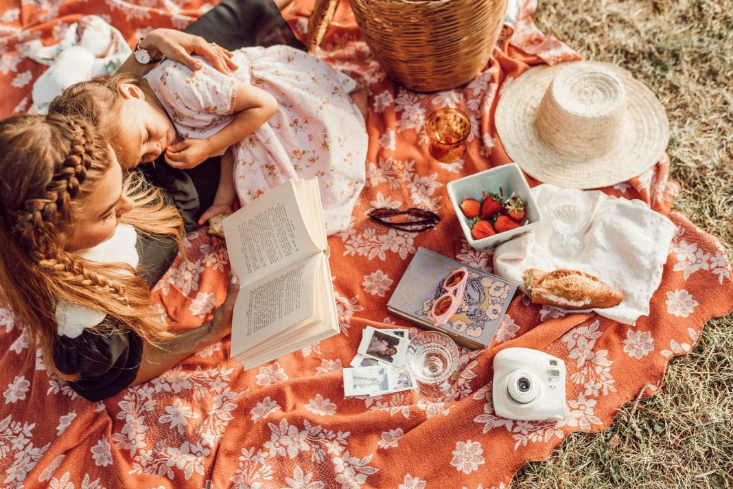 Mom reading to daughter on a picnic blanket